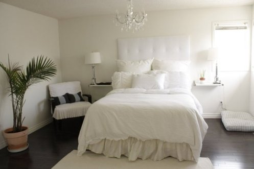 white bedroom with chandelier and pot palm
