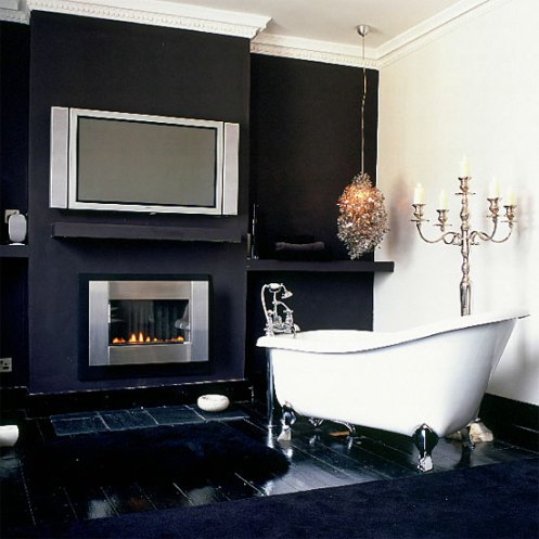 black and white bathroom with tv, fireplace and chandelier