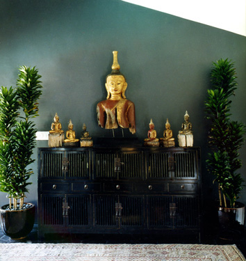 hallway entry blue green gery with black chest and gold buddha and black cabinet