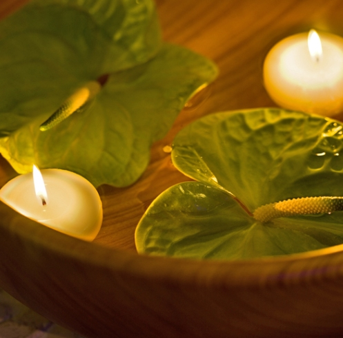 wooden bowl with lilly leaves and floating candles