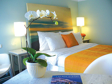white yellow blue modern beach style bedroom, sunset painting headboard, white orchid