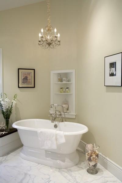 classic posh bathroom with chandelier, tub, marble floor, cream color
