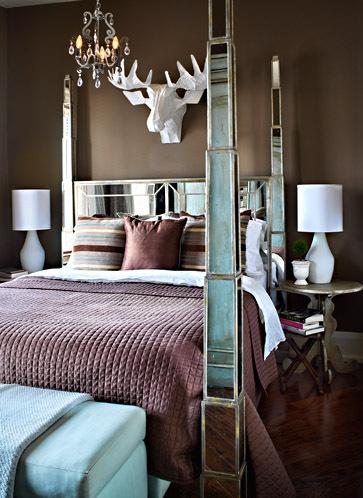 brown and blue bedroom with mirrored bed and white mosse head, bedroom chandelier