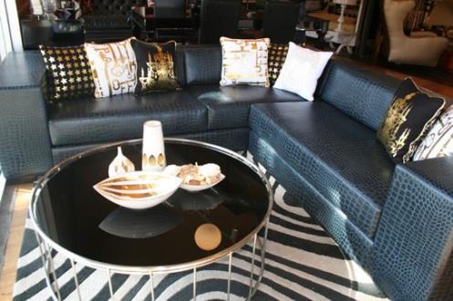 black and gold retro modern living room, black crock couch, zebra rug