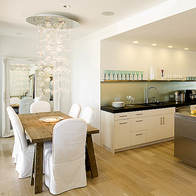 white modern kitchen and dining area with chandelier