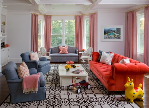 colorful modern living room white walls, blue sofa, red soda, bold pattern rug