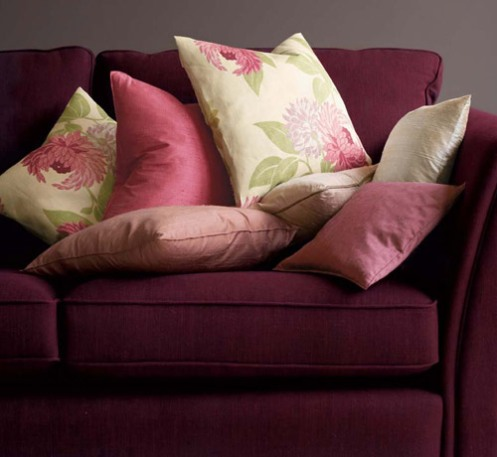 purple sofa couch with rose fabric pillows